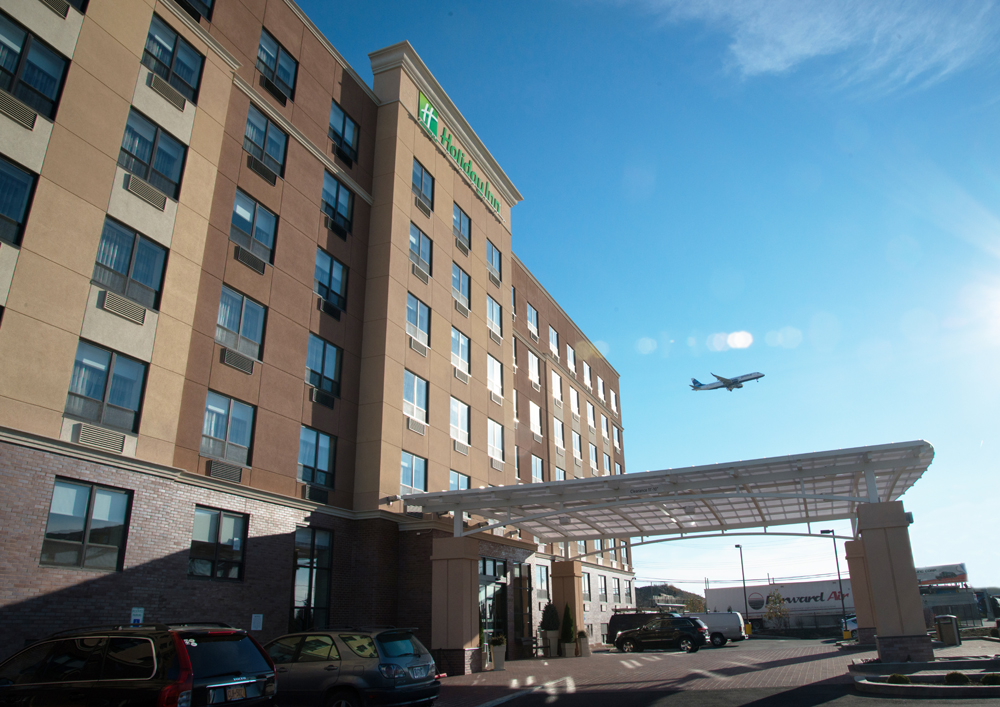 Holiday Inn New York JFK Airport Area exterior front entrance daytime with plane overhead