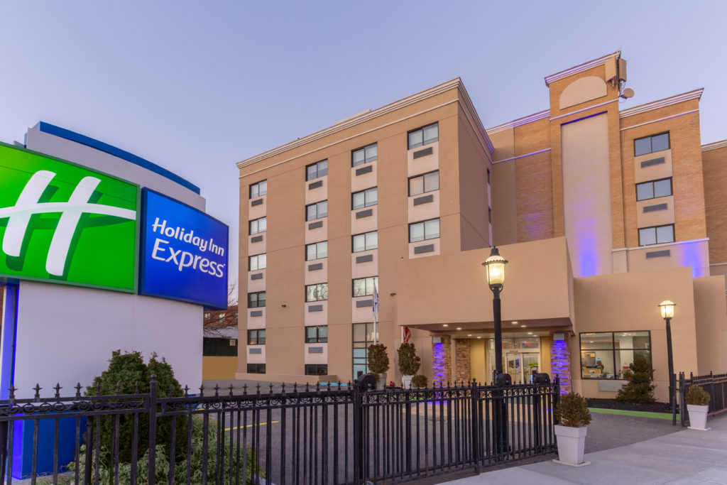 Holiday Inn Express LaGuardia Airport exterior with sign in evening